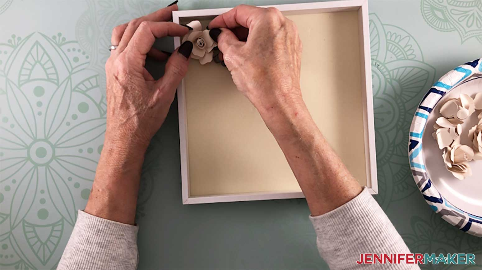 Gluing the paper flowers inside the shadow box