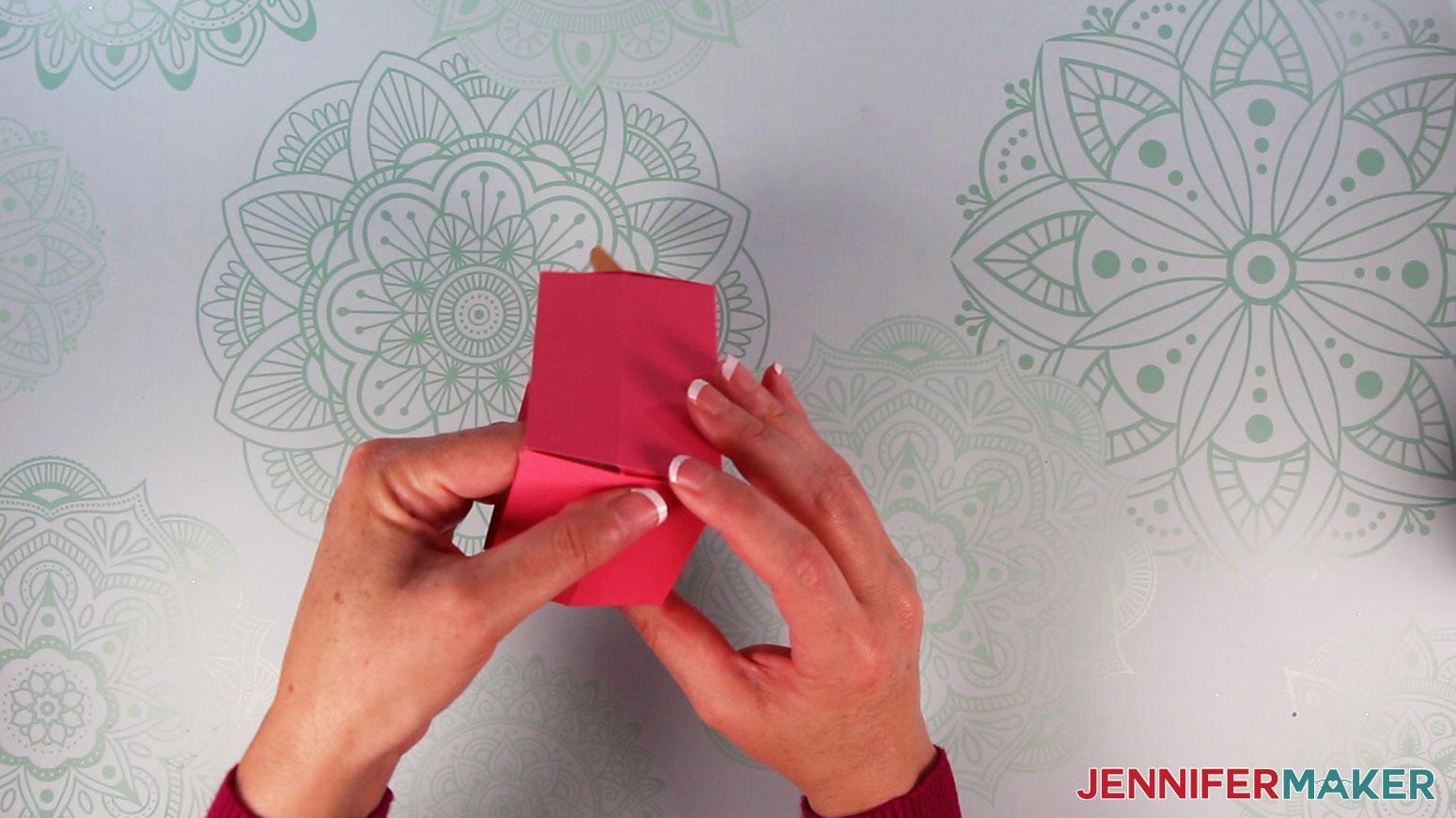 Apply pressure to popsicle box until glue adheres