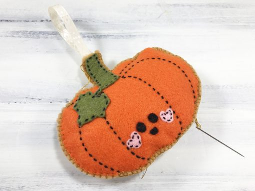 Insert ribbon into the top of your felt pumpkin and sew closed