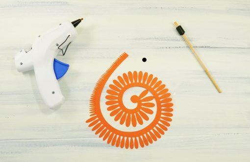 Materials for making a paper daisy: paper, hot glue gun, quilling tool