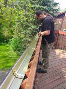 Drilling water drainage holes in the gutter garden on our deck