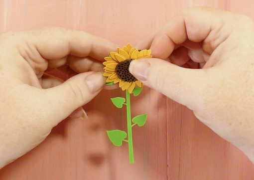 Glue the rolled paper sunflower to the stalk