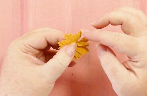 Opening up the petals of the rolled paper sunflower