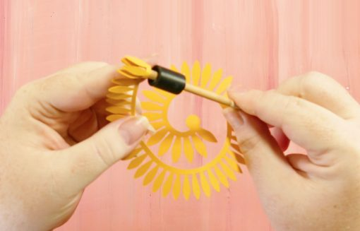Insert the tip of the rolled paper sunflower into the quilling tool
