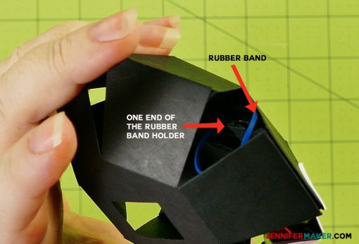 Place the rubber band in the head of the penguin paper bomb
