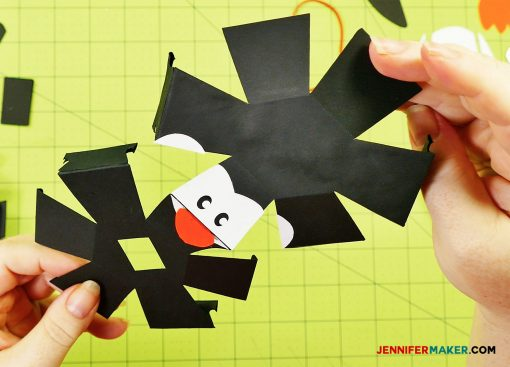 Sandwich the bill in between the top and bottom face pieces of your penguin paper bomb