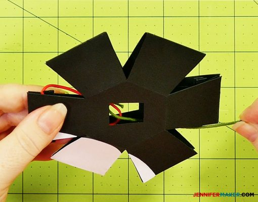 Place the rubber band in the body of the penguin paper bomb