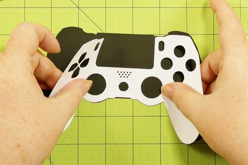 Attach the white controller to the black controller of the popup game controller card