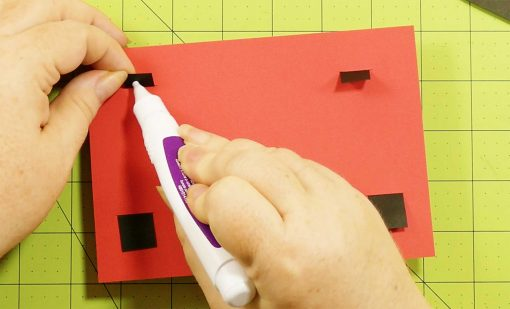 Glue down the tabs for the pop-up game controller card