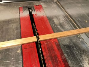 Cutting the shoe moulding strips to size on the table saw