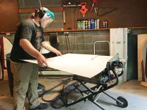 Cutting the white panelboard to size on the table saw