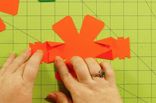 Fold the triangles in on the top piece of the pumpkin paper bomb