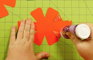Glue down the triangle sides on the pumpkin paper bomb
