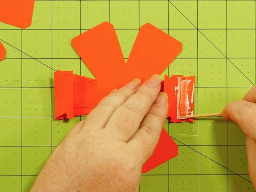 Gluing the rubber band holders on the pumpkin paper bomb