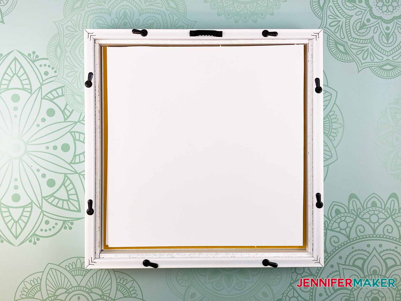 Add foam core to the back of the picture frame to prevent the stacked layers from moving