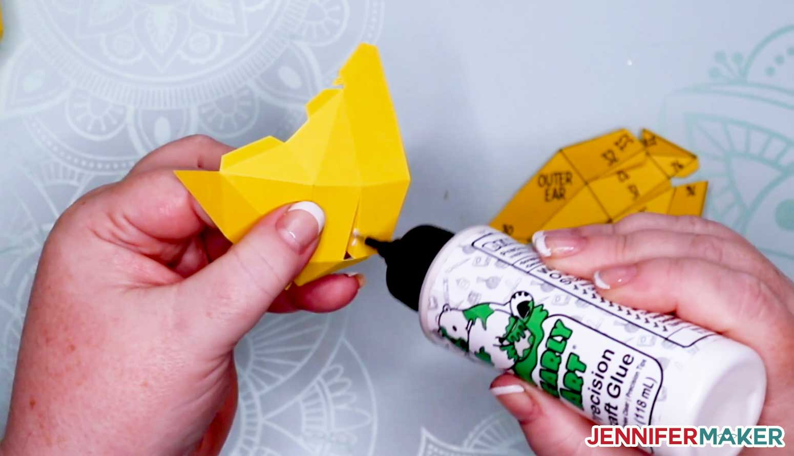 Gluing the outer ear of the 3D cat in yellow cardstock with Bearly Art glue