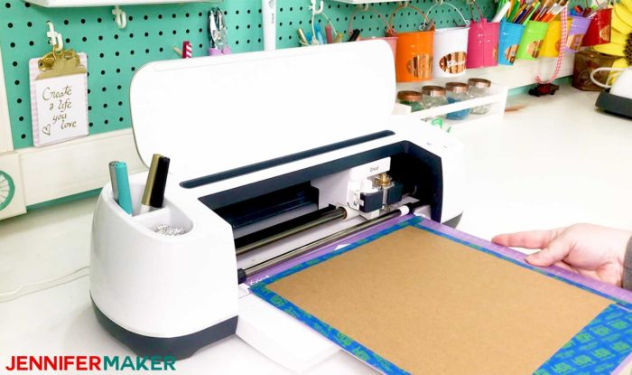 Heavy chipboard taped to a StrongGrip mat and loading into a Cricut Maker for the Cricut Tool Holder