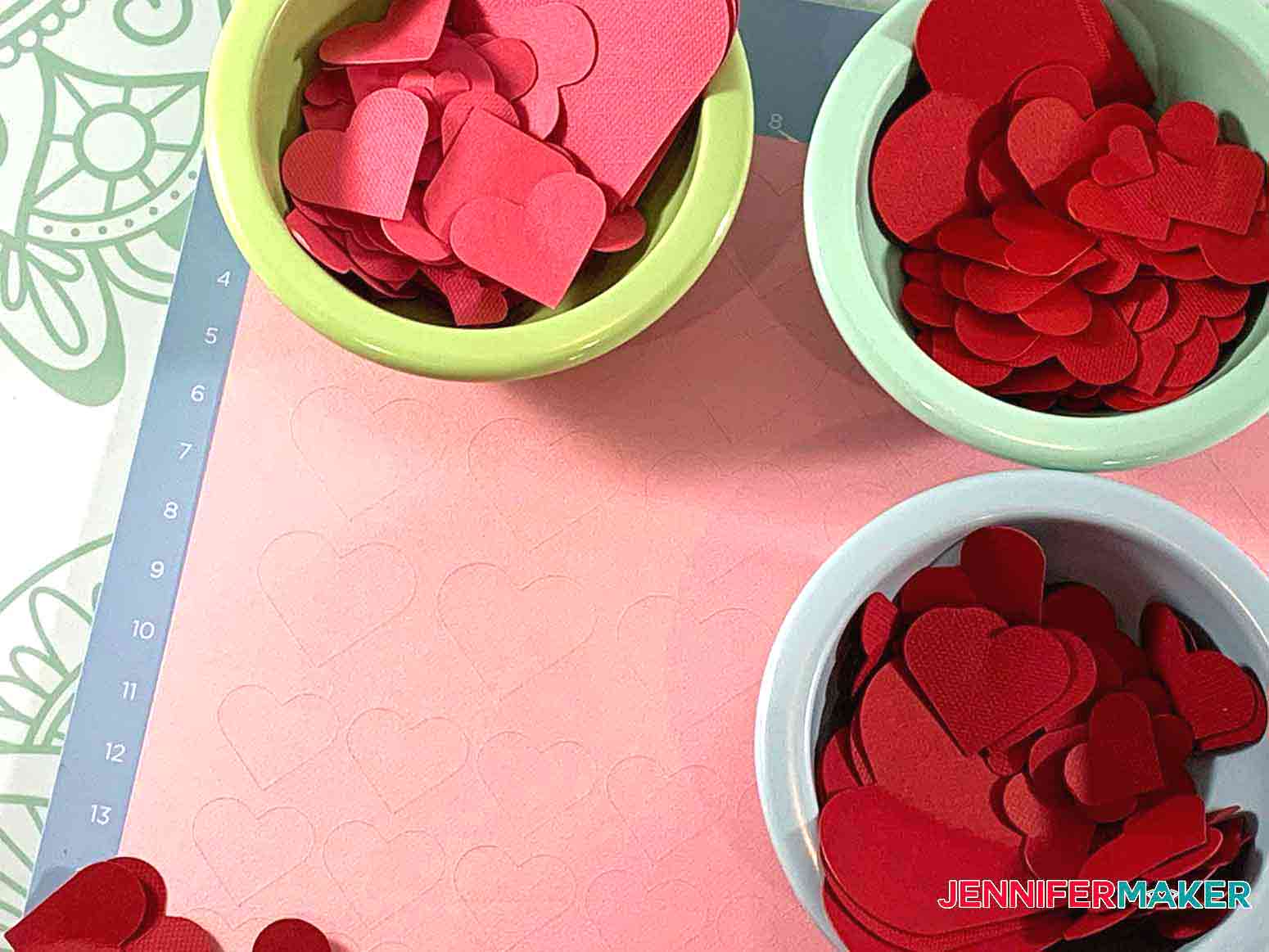 Paper Hearts cutout on Cricut LightGrip mat in four different shades of red for Easy Paper Heart Tree by JenniferMaker