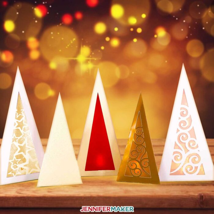 Pretty paper Christmas tree luminaries aglow against a magical backdrop