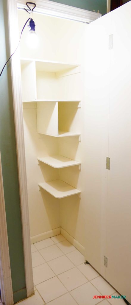 Floating shelves painted white in the cleaning closet