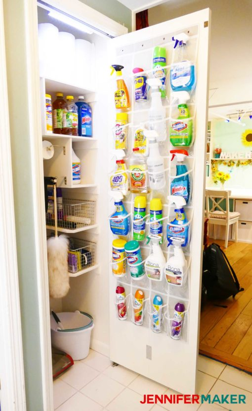 A well stocked and organized cleaning closet with light, door holder, bag holders, and broom holders