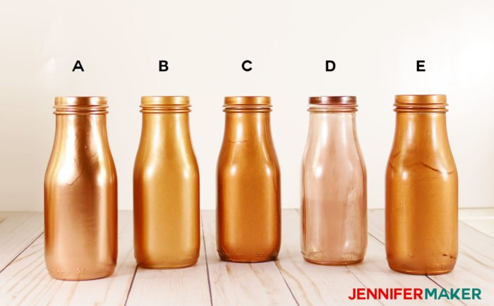Copper spray paint on glass bottles shows difference in color hue, shine, and coverage