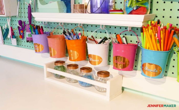 Colorful buckets hanging on my giant craft room pegboard