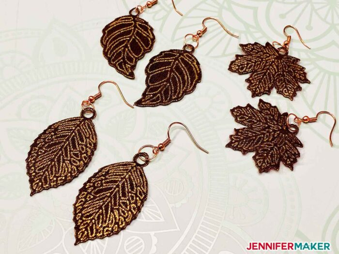 Gold Cricut Foil Transfer Sheet on Brown Faux Leather with a Wood Grain to make leaf earrings