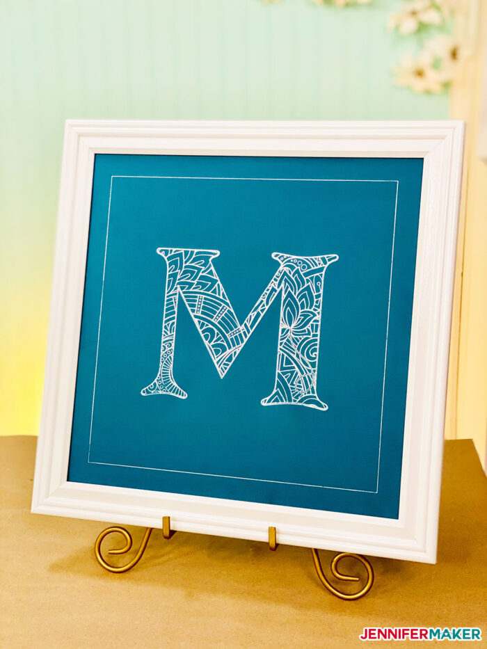 Beautiful foil mandala letter in silver foil on blue cardstock with a white frame