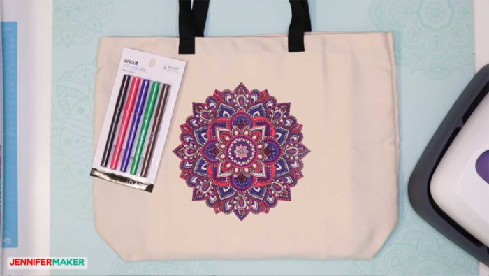 A totebag with an Infusible Ink coloring projects -- a mandala in pink and purple -- on the front