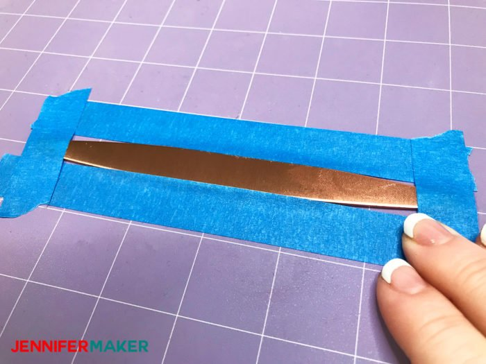 Taping a copper bracelet to a purple Cricut StrongGrip Mat to keep it from moving when we use the Cricut Maker Engraving Tool