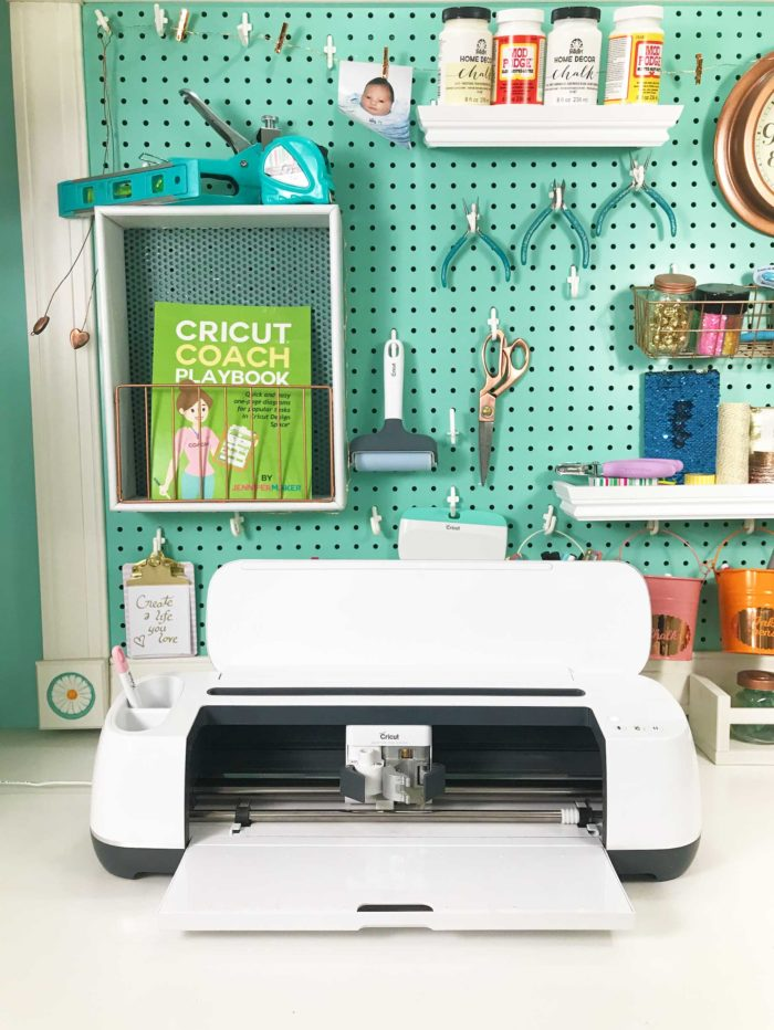 My Cricut Maker in front of my giant pegboard in my craft room