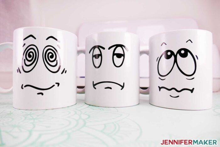 Cricut mugs with funny pre-coffee faces cut in black vinyl and sealed with dishwasher safe mod podge