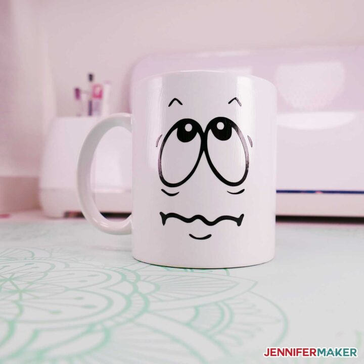 Cricut mug with funny faces in vinyl and made dishwasher safe with mod podge