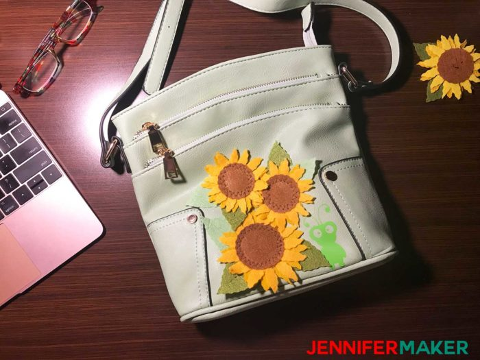 Green purse covered in felt sunflowers and a vinyl Cricut cutie