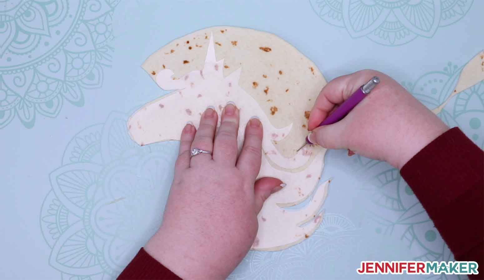 Cutting the tortilla with a knife using the Cricut stencil cut from plastic