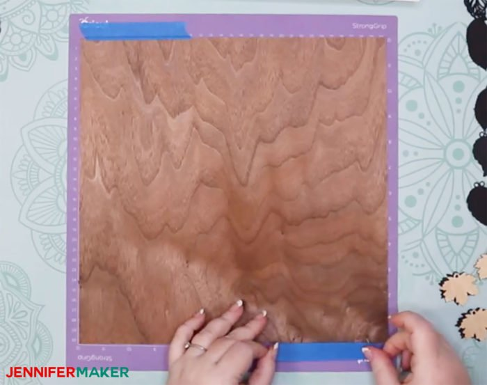 Taping the Cricut Wood Veneer to the Strong Grip Mat with Painter's Tape