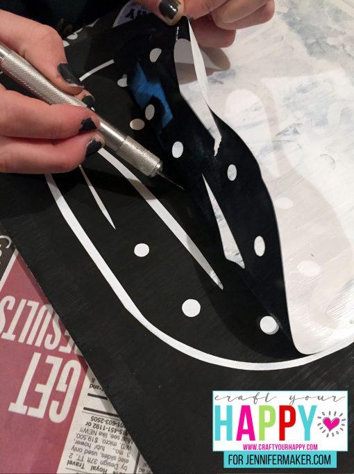 Lifting up the stencil for the DIY Christmas Mason Jar Snowglobe Chalkboard Sign