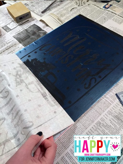 Pressing down the stencil on the board for the DIY Christmas Mason Jar Snowglobe Chalkboard Sign