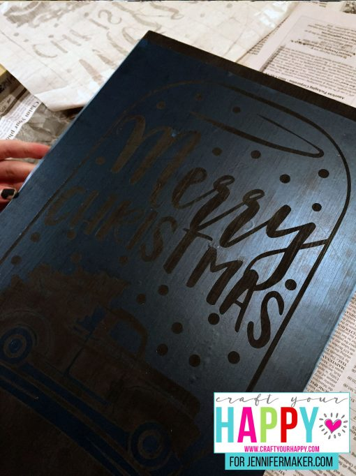 The stencil in place on the board for the DIY Christmas Mason Jar Snowglobe Chalkboard Sign