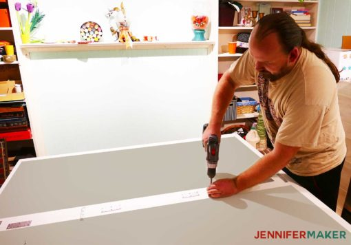 Attaching the two tabletops together with brackets to create the diy craft table with storage