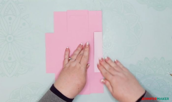 Folding a pink piece of cardstock cut into a DIY drawer divider box