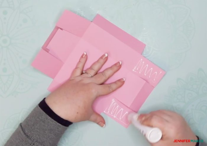 Glueing the sides on a pink piece of cut cardstock to make a DIY drawer divider
