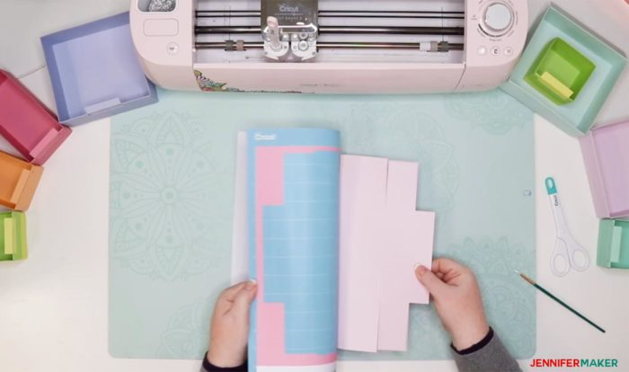 Gently peeling a cutting mat away from a piece of pink cardstock that has been cut on a Cricut to make a DIY drawer divider to organizer a drawer
