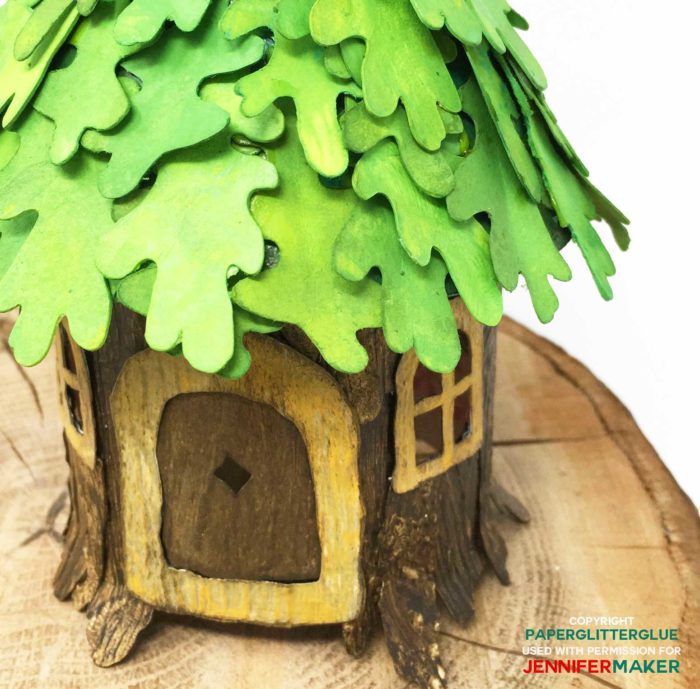 Paper leaves over a paper tree stump to make a DIY fairy house