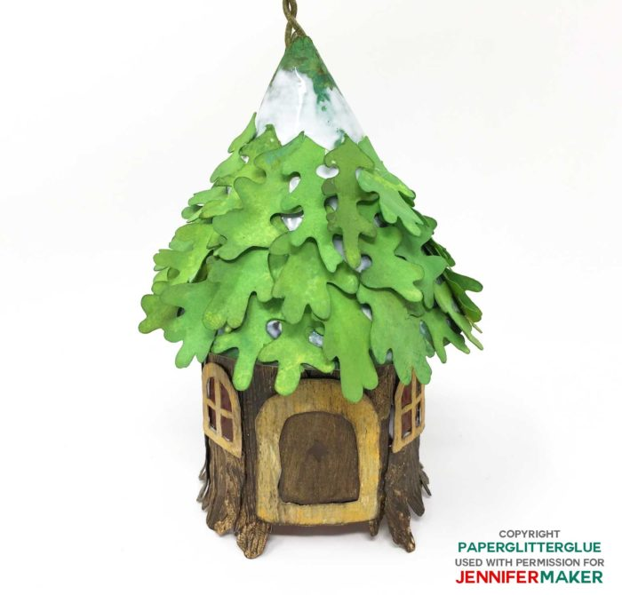 Gluing leaves onto the roof of the paper fairy house tree stump