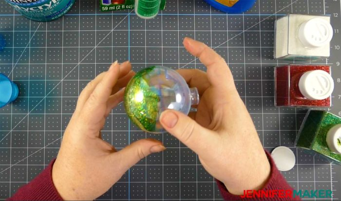 Swirling green glitter around the inside of a clear ornament to make DIY glitter ornaments