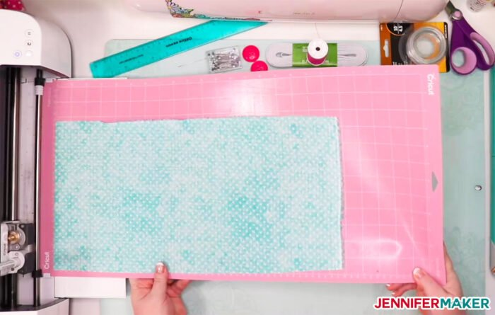 Loading fabric on a pink FabricGrip mat in to a Cricut Maker to make DIY headbands with buttons for masks
