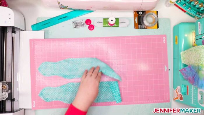 Removing the cut fabric from the pink FabricGrip mat to make DIY headbands with buttons for face masks