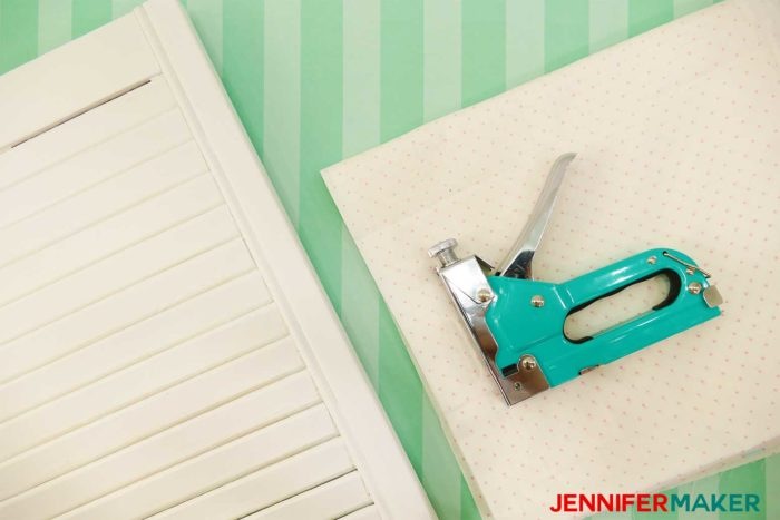 An old white shutter, material, and a staple gun are the materials you need to make a DIY Paper Organizer from a Repurposed SHutter